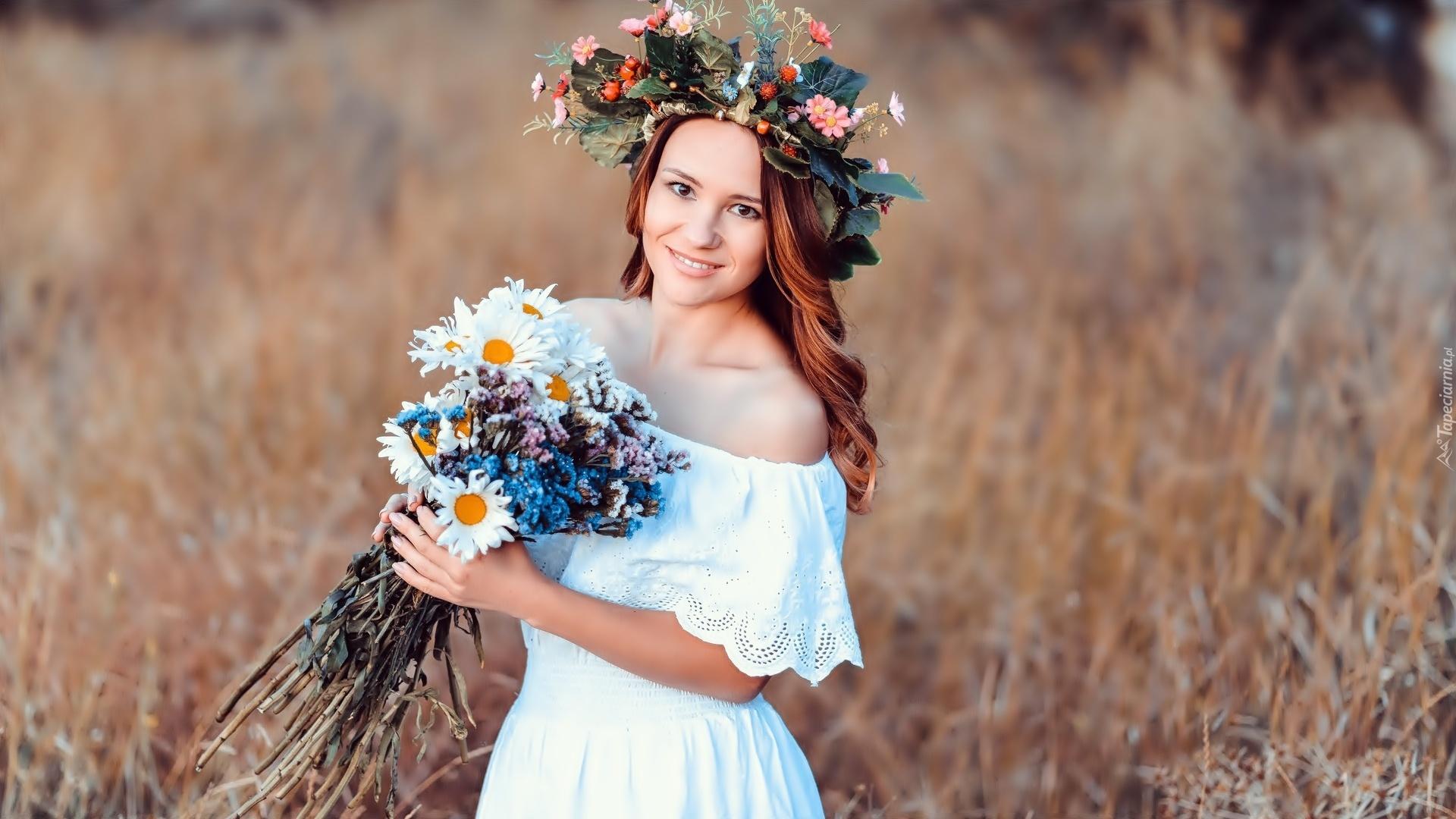 Dziewczyna z bukietem polnych kwiatów na łące