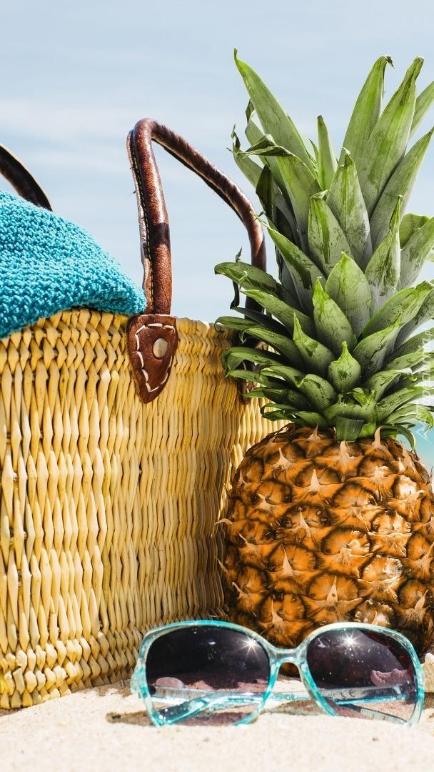 Ananas obok koszyka i okularów