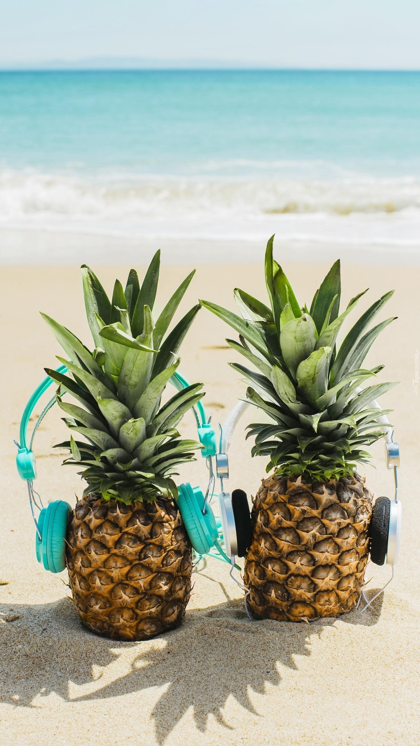 Ananasy ze słuchawkami na plaży