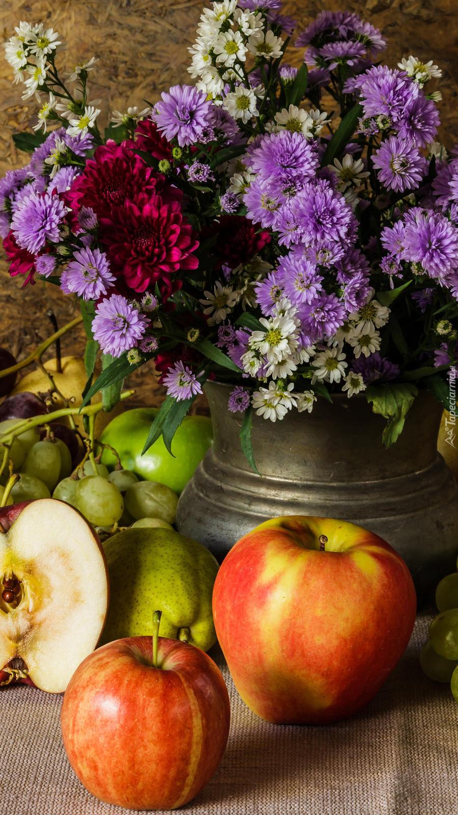 Astry marcinki w dzbanku obok owoców