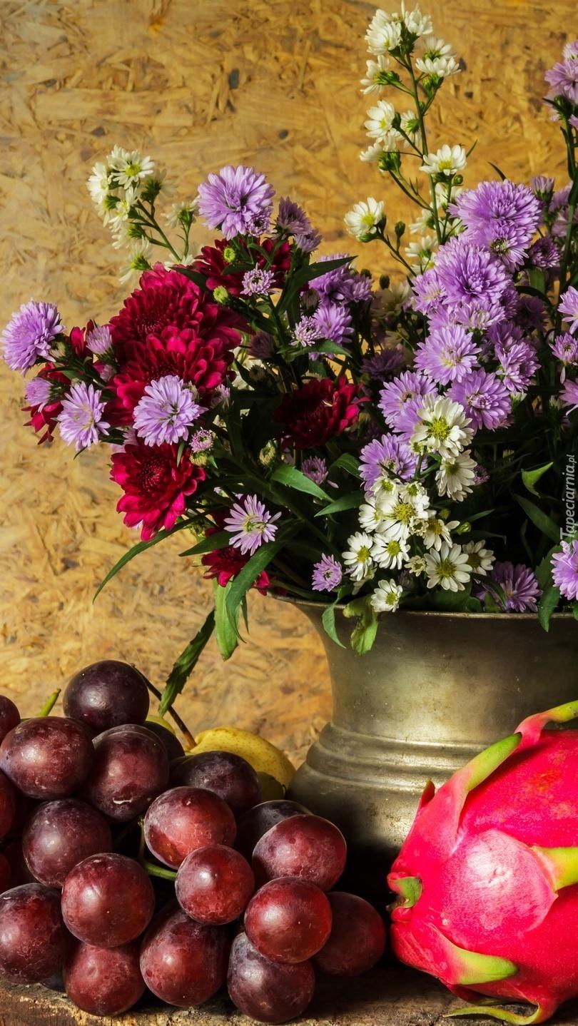 Astry marcinki w wazonie obok winogron