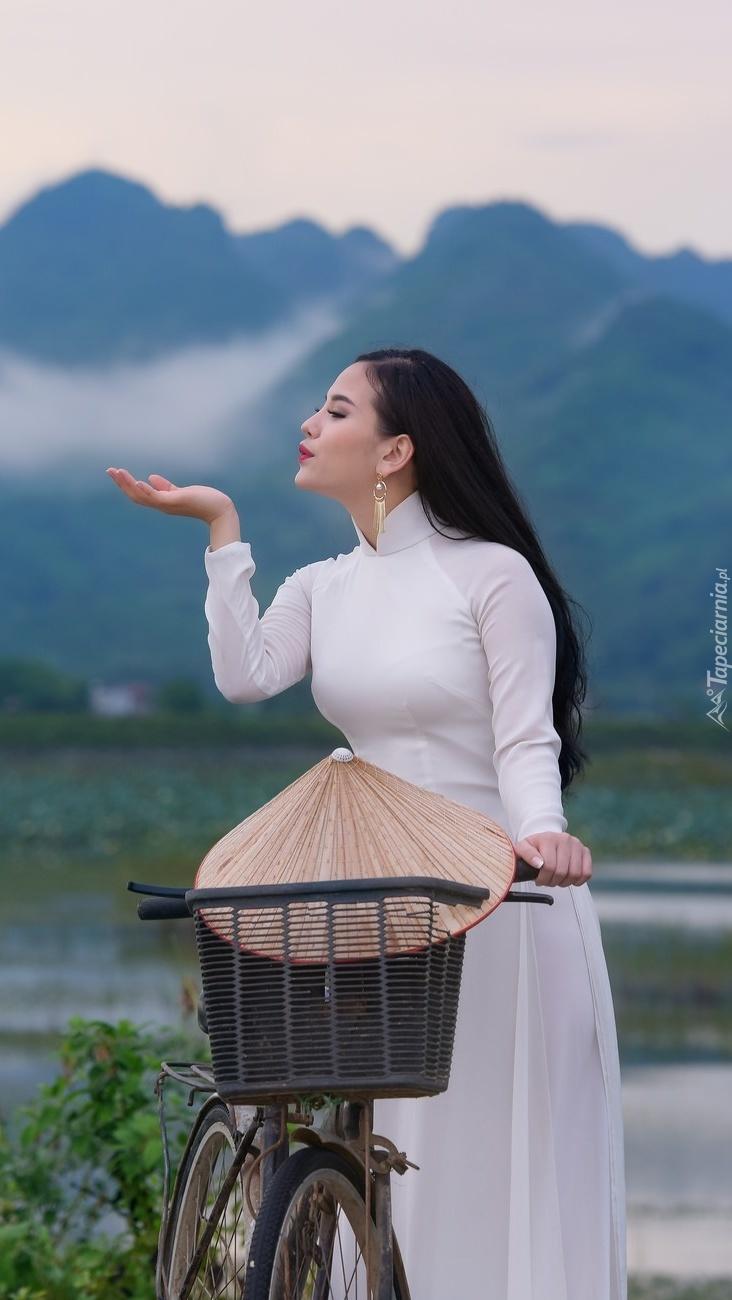Azjatka w białej sukni przy rowerze