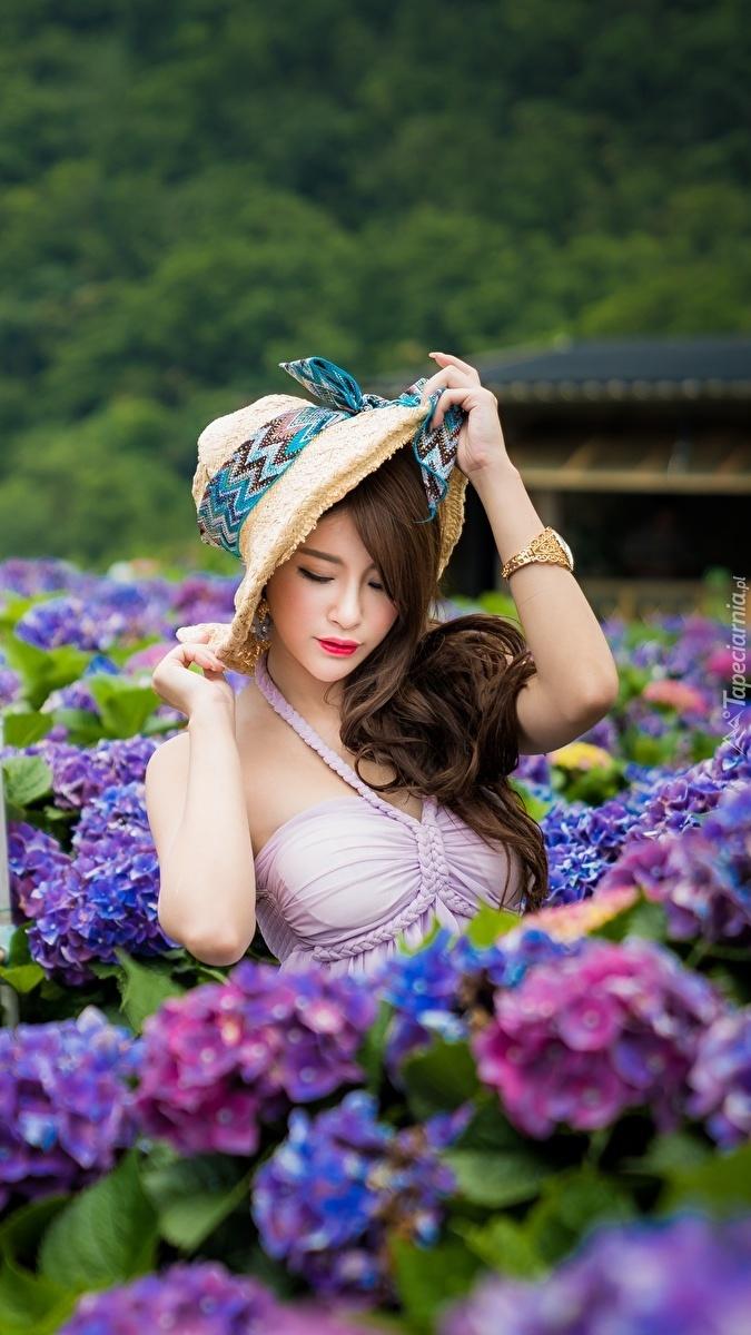 Azjatka wśród kwiatów hortensji
