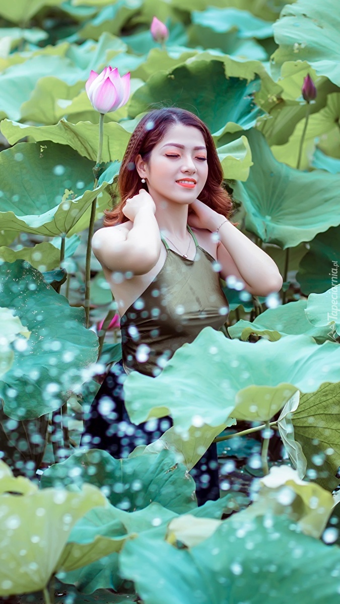 Azjatka wśród liści i kwiatów lotosu