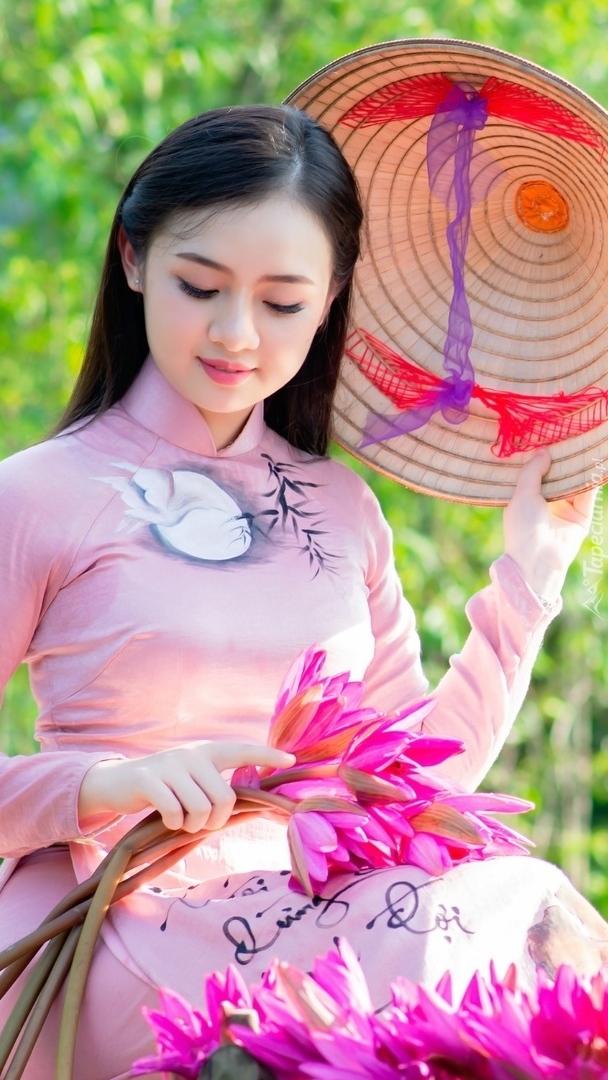Azjatka z kapeluszem i kwiatami