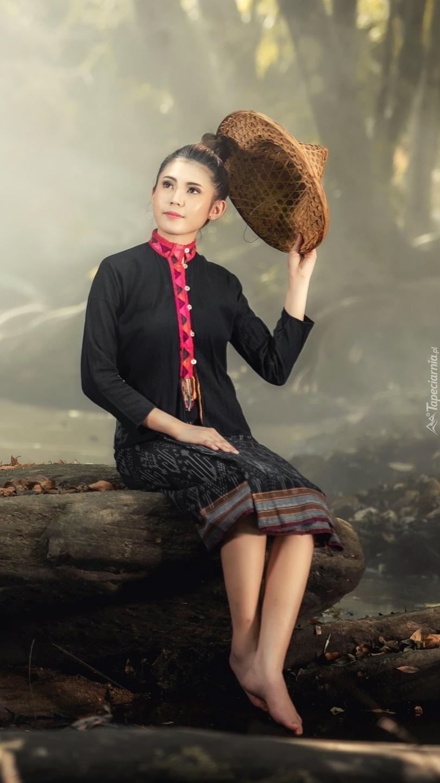Azjatka z kapeluszem w ręce