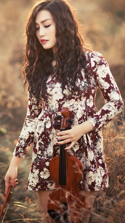 Azjatka ze skrzypcami na łące