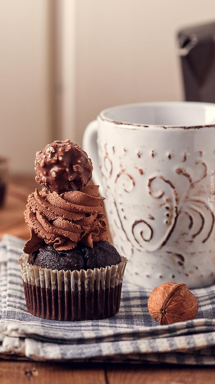 Babeczka czekoladowa obok kubka