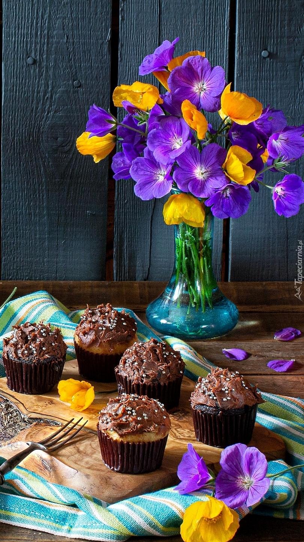 Babeczki na desce obok kwiatów w wazonie