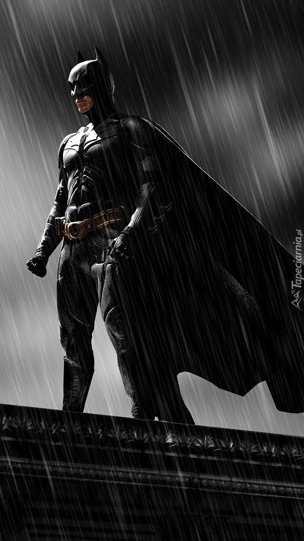 Batman na dachu w deszczu