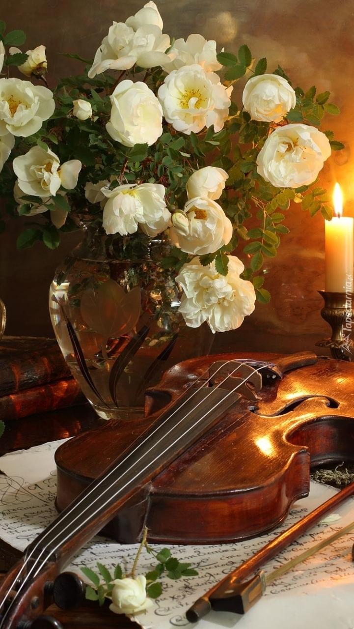 Białe róże w wazonie obok skrzypiec