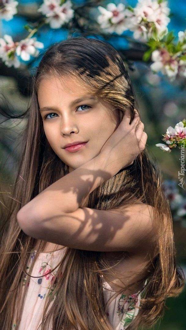 Blondwłosa dziewczyna pod wiosennym drzewem