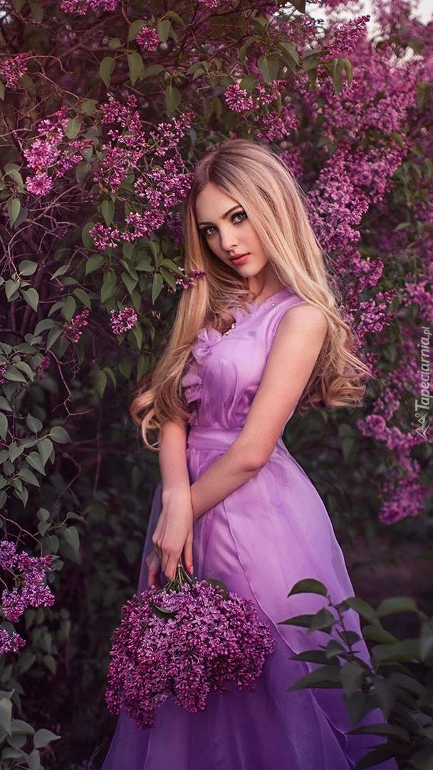 Blondynka na tle kwitnącego bzu