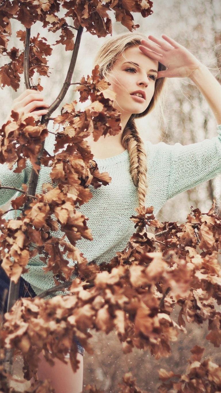Blondynka z warkoczem pośród liści