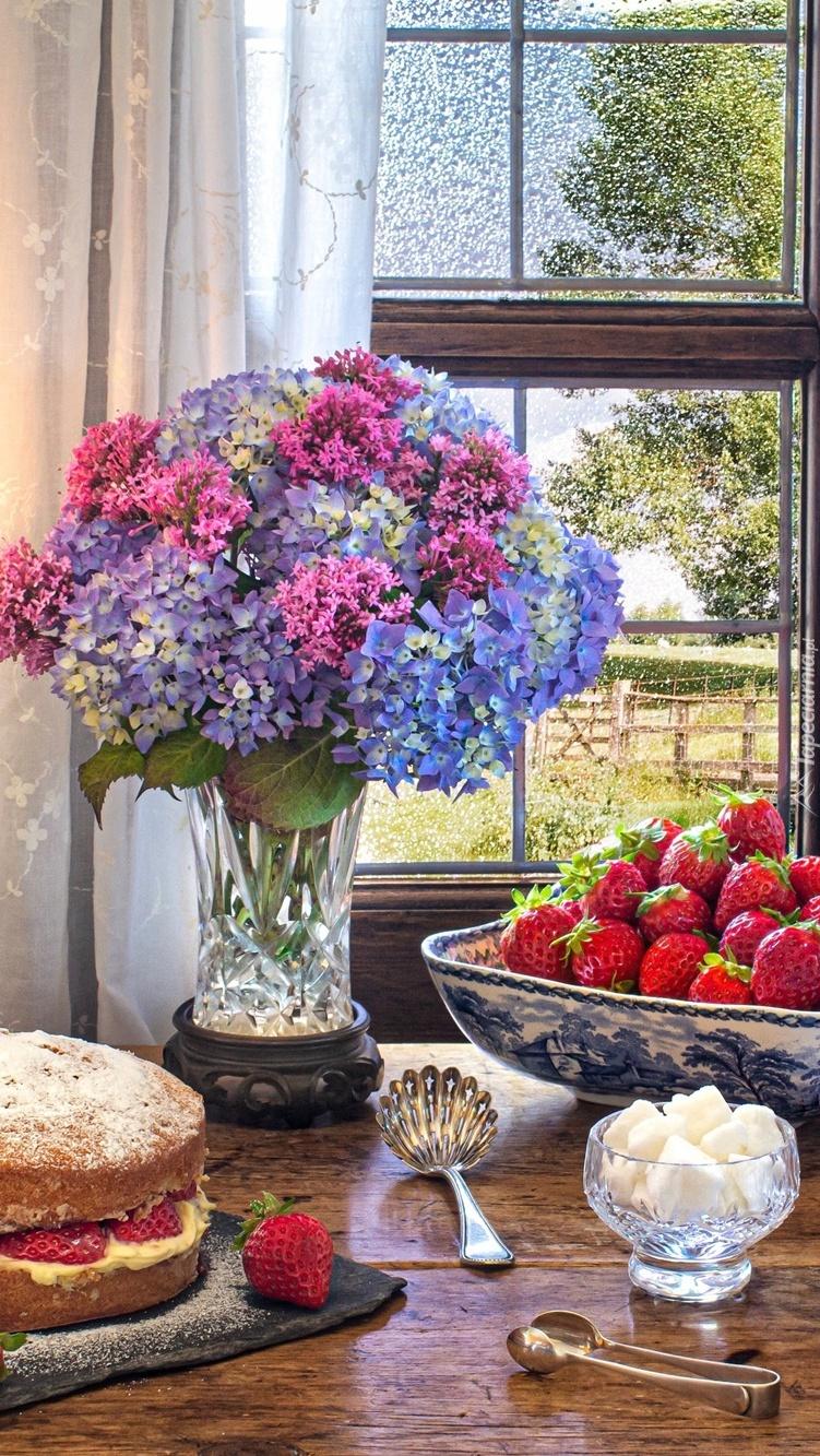 Bukiet kwiatów obok ciasta i truskawek przy oknie