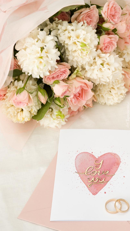 Bukiet kwiatów obok kartki i obrączek