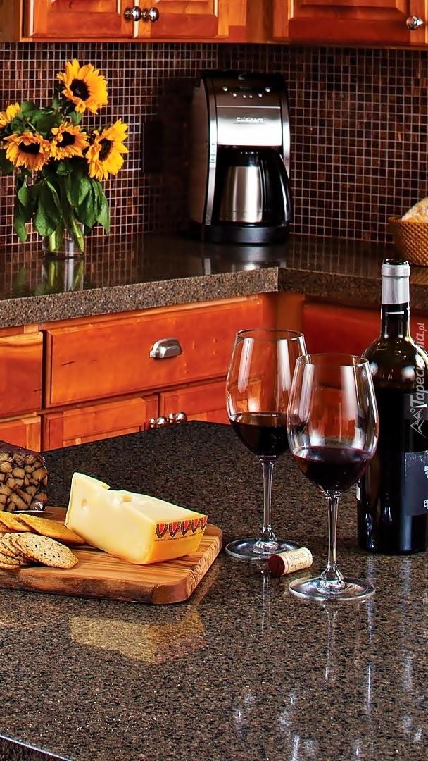 Butelka wina, kieliszki i ser na blacie w kuchni