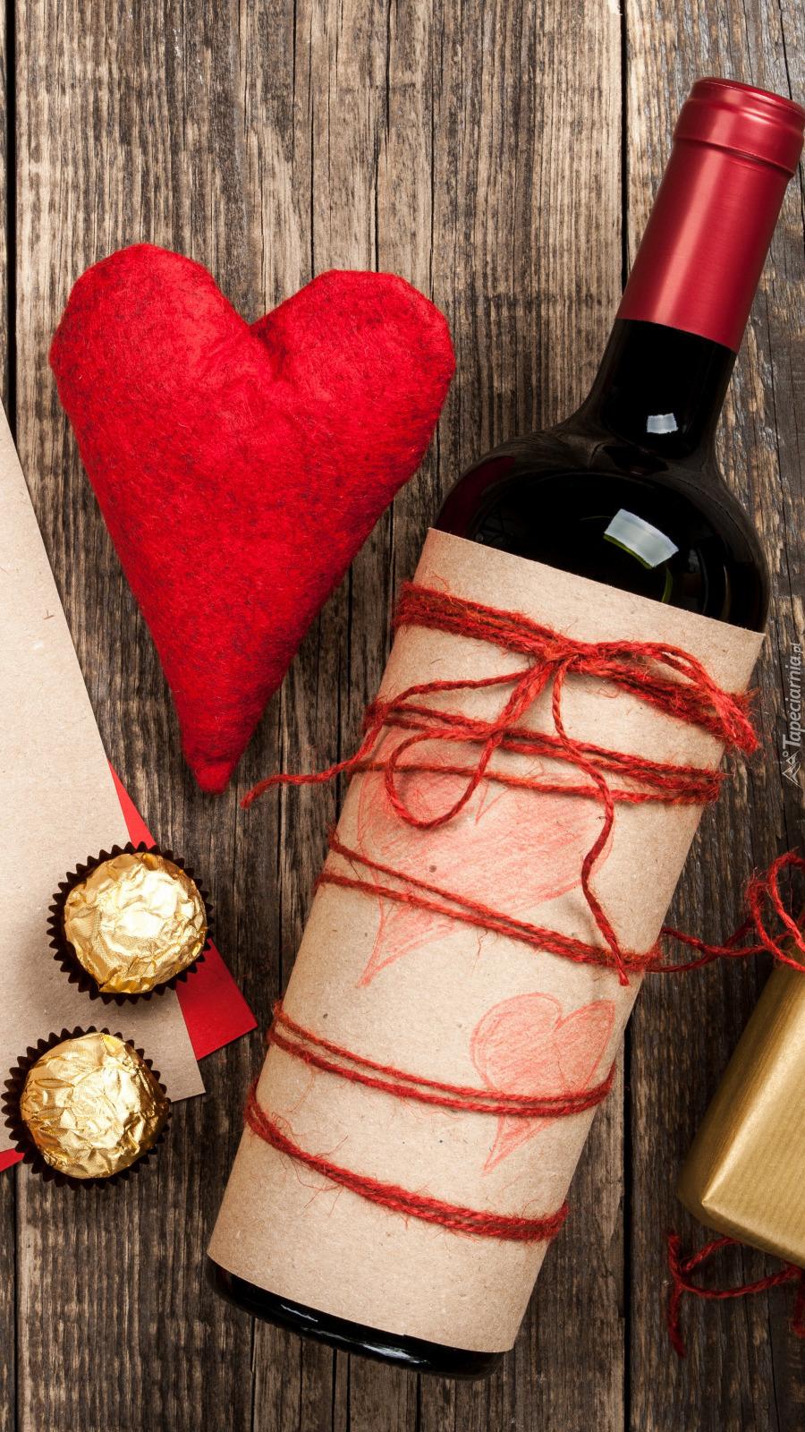 Butelka wina obok serca i czekoladek