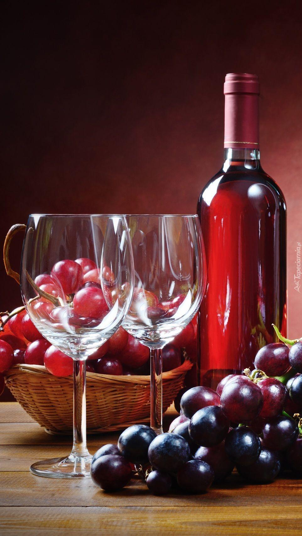 Butelka wina z dwoma kieliszkami i winogrona
