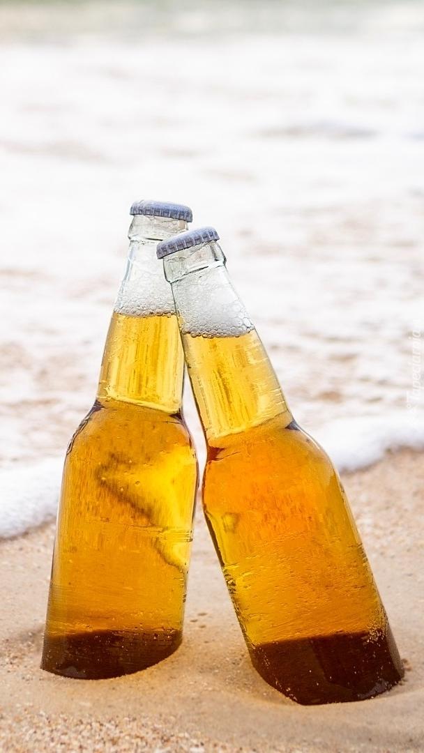 Butelki piwa w piasku