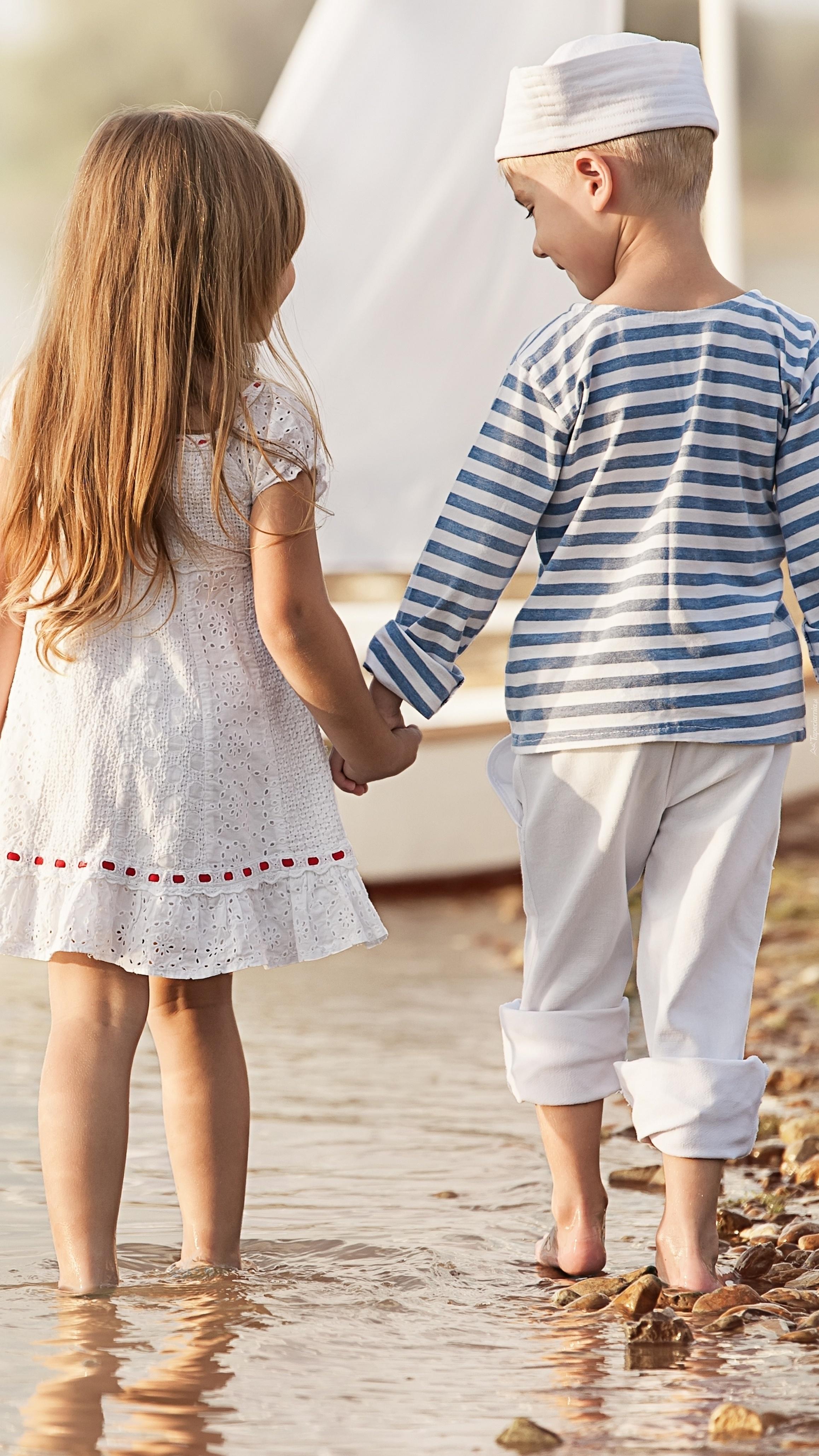 Chłopczyk i dziewczynka na spacerze brzegiem morza