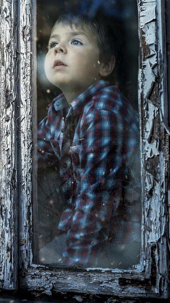 Chłopczyk patrzy przez okno