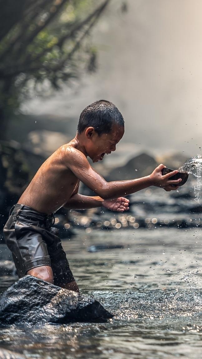 Chłopiec bawiący się w rzece