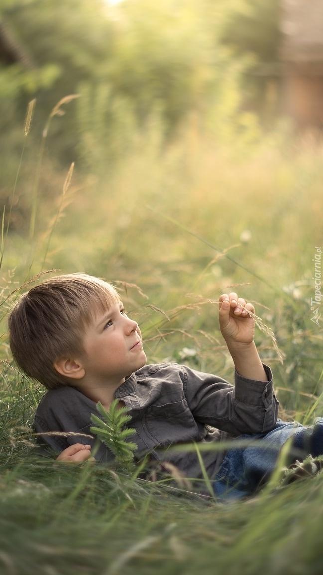Chłopiec leżący w trawie