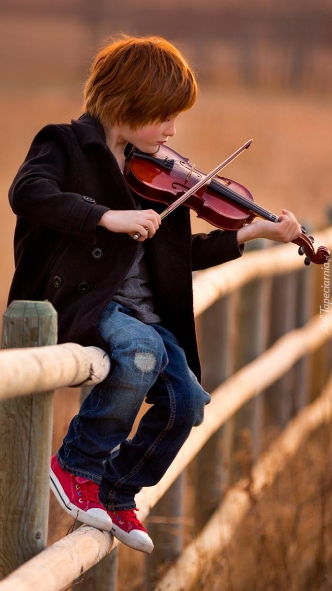 Chłopiec siedzący na ogrodzeniu i grający na skrzypcach
