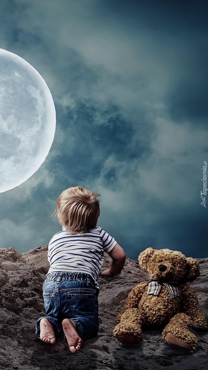 Chłopiec z pluszakiem patrzący na księżyc