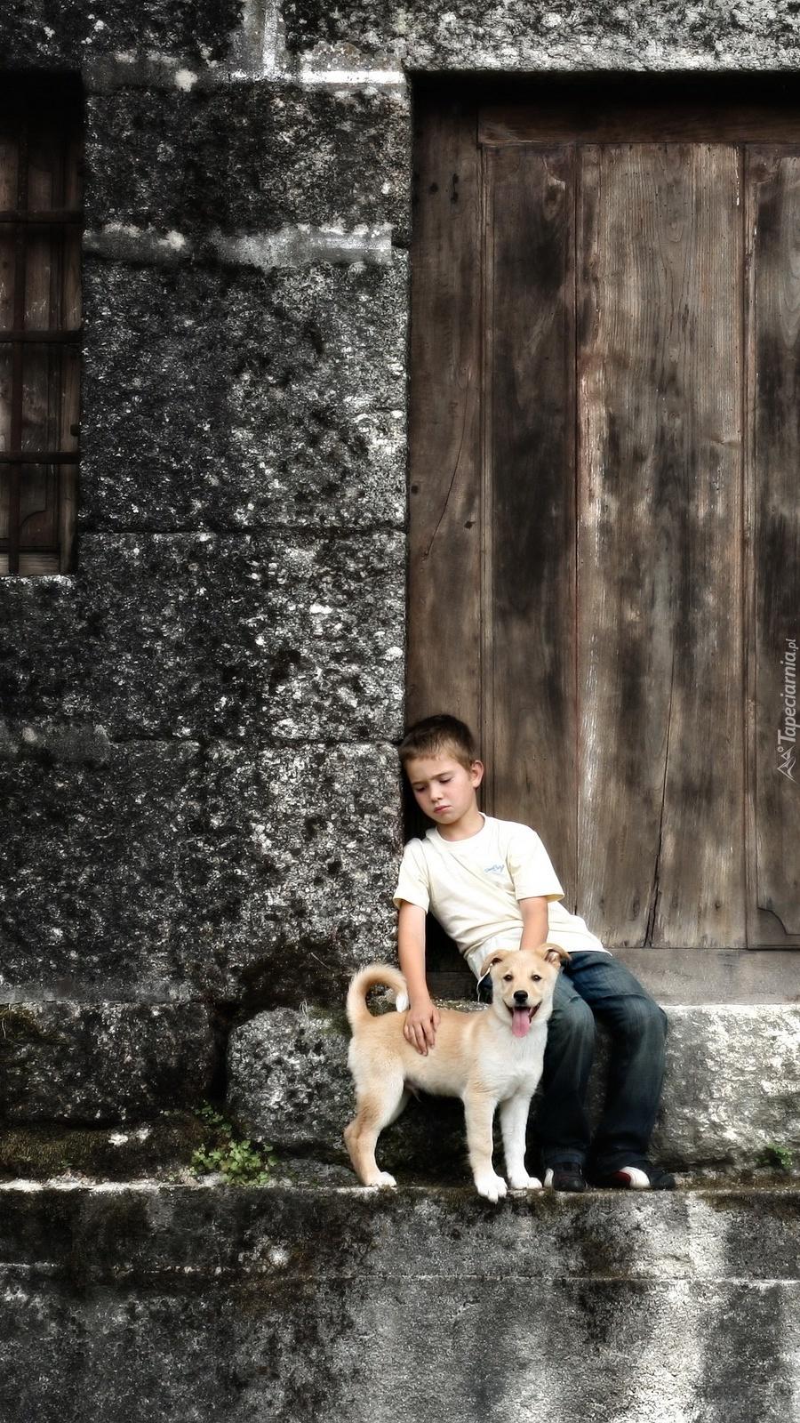 Chłopiec z psem na progu domu