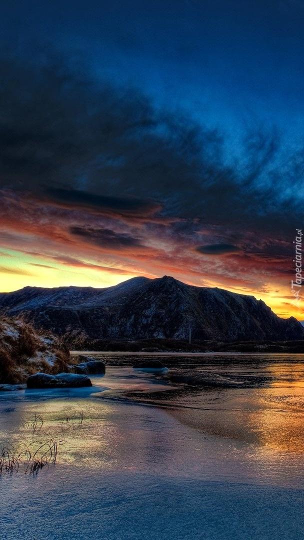 Chmury nad górskim jeziorem o zachodzie słońca