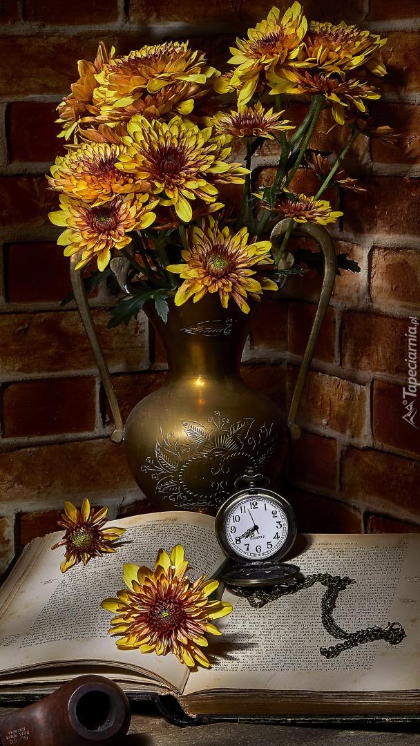 Chryzantemy w wazonie obok książki i zegarka