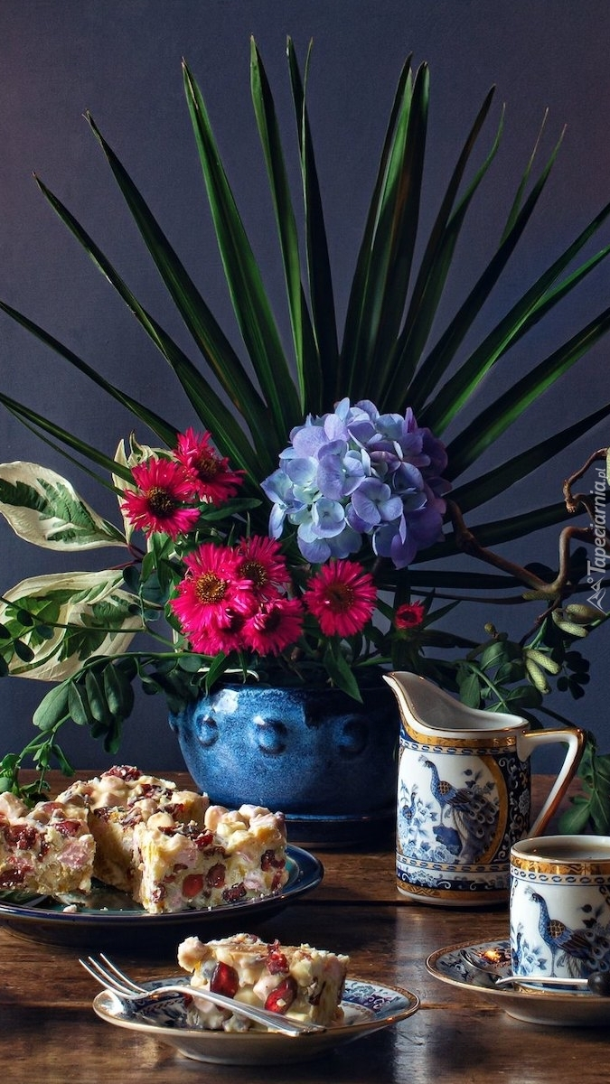 Ciasto na talerzykach obok kwiatów w wazonie