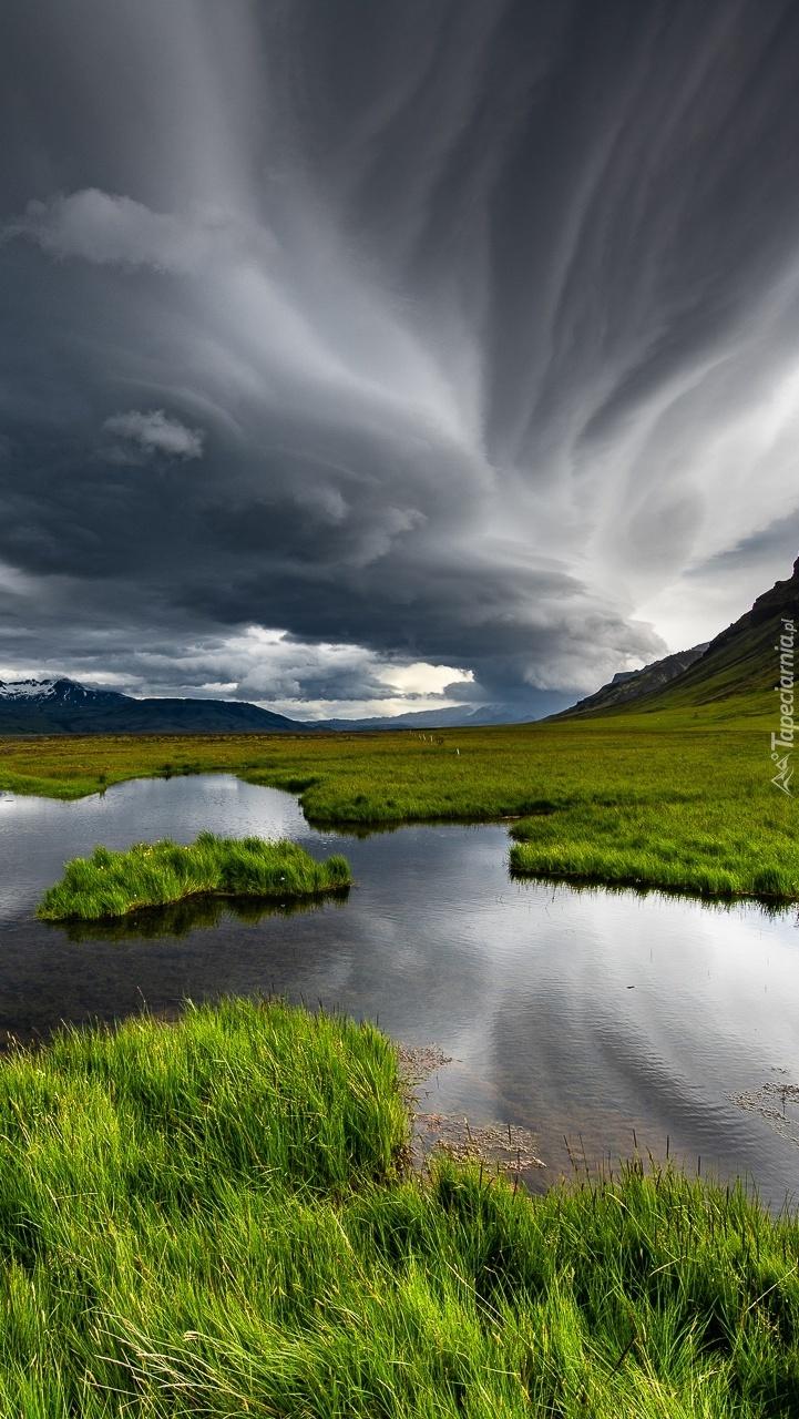 Ciemne chmury nad łąkami i jeziorem