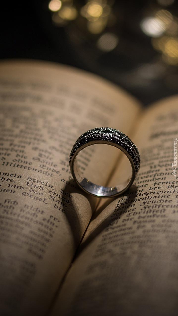 Cień pierścionka na kartkach książki