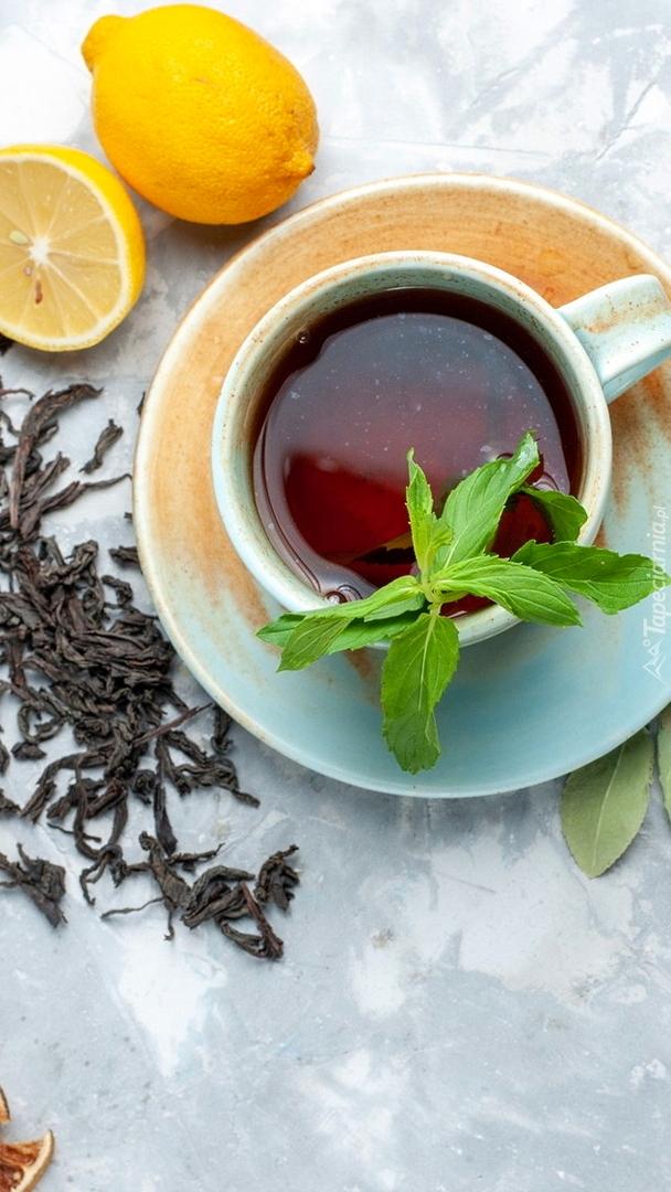 Cytryny obok filiżanki herbaty z miętą