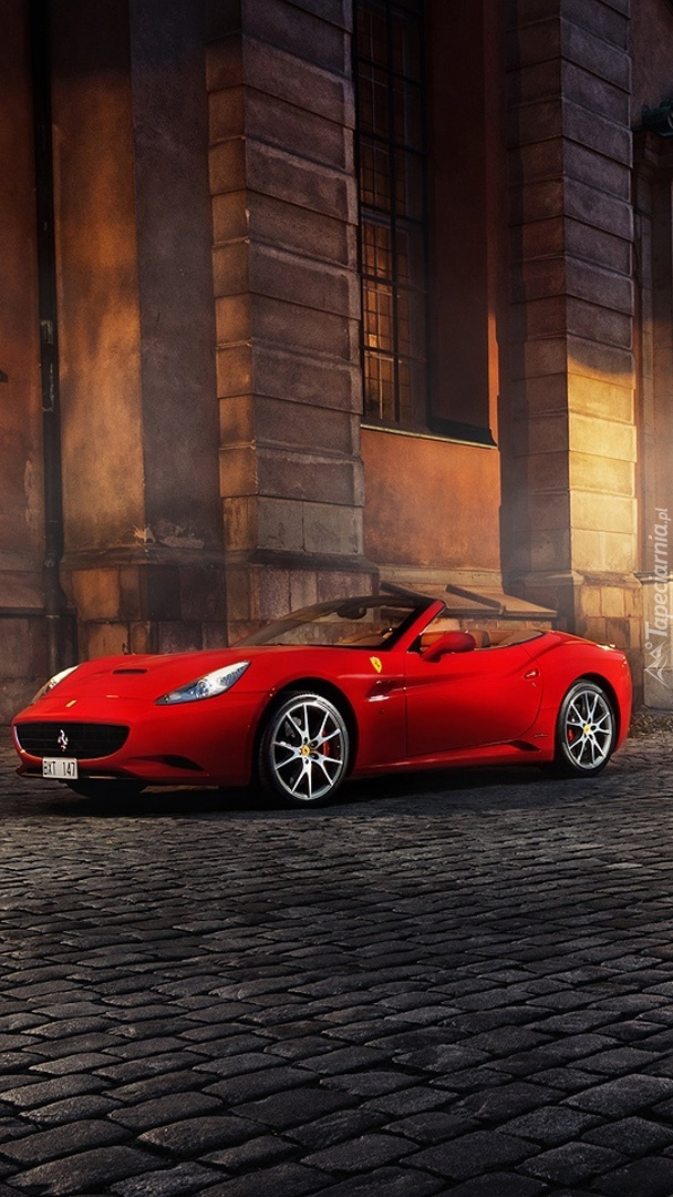 Czerwone Ferrari przed budynkiem