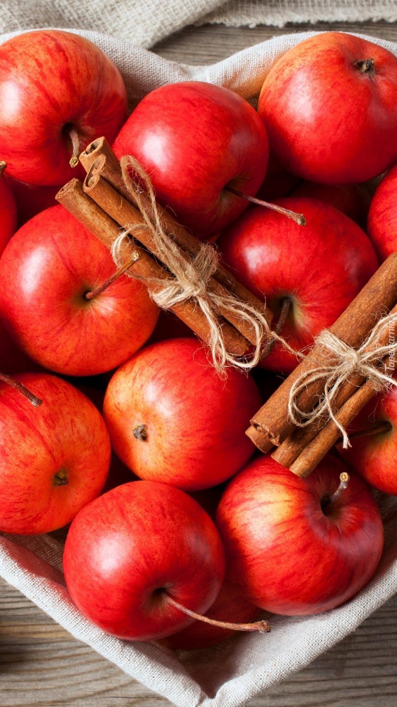Czerwone jabłka i laski cynamonu