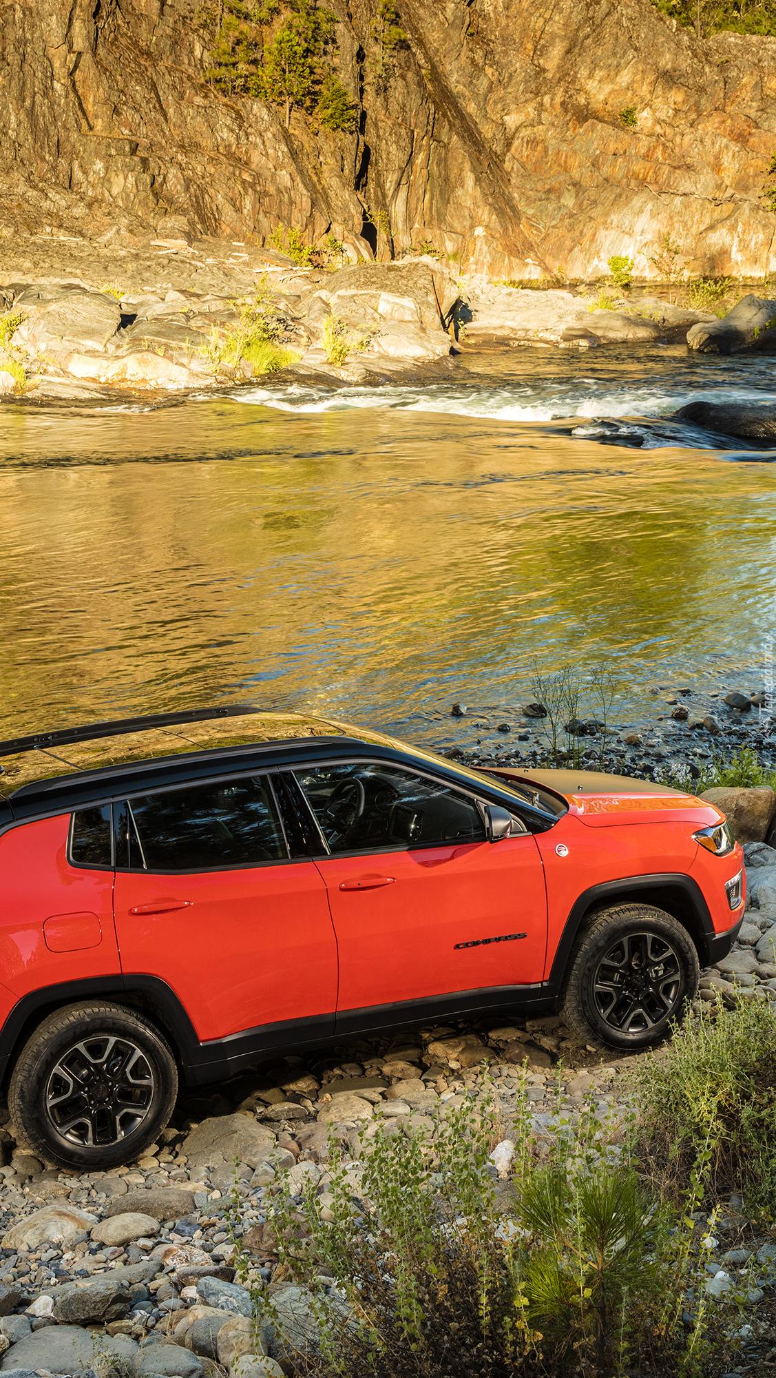 Czerwony Jeep Compass na brzegu rzeki