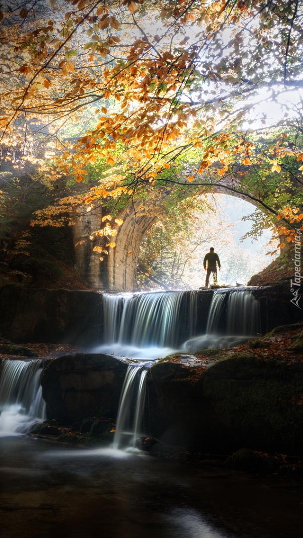 Człowiek na skale przy moście