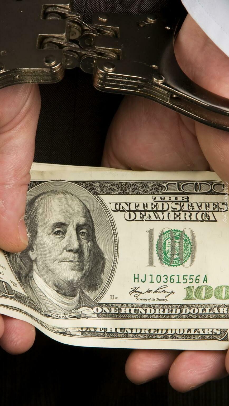 Dłonie w kajdankach z dolarami