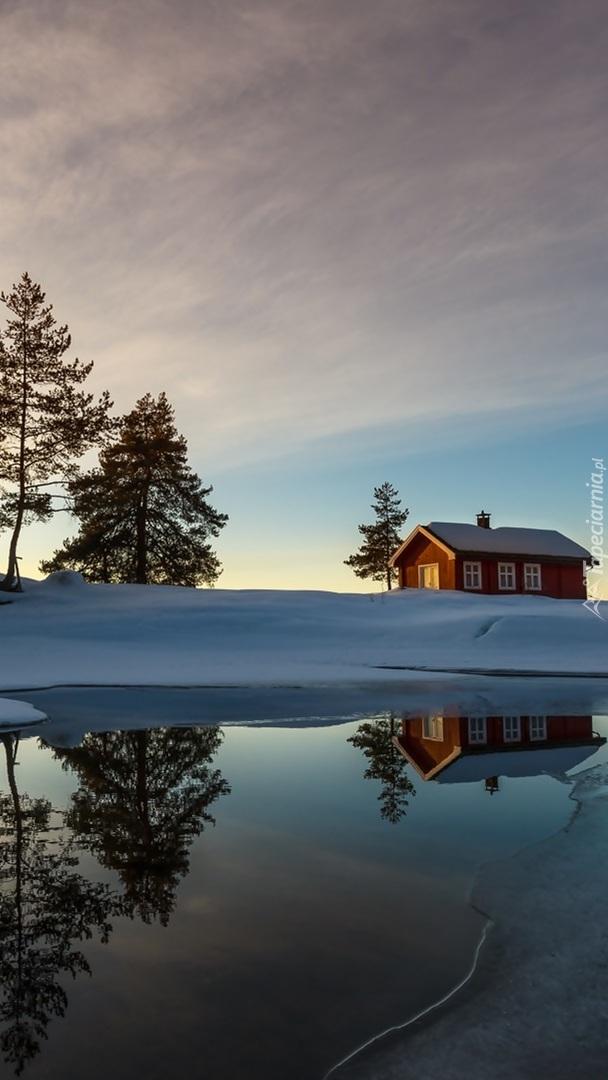 Dom i drzewa w śniegu nad jeziorem Vaeleren