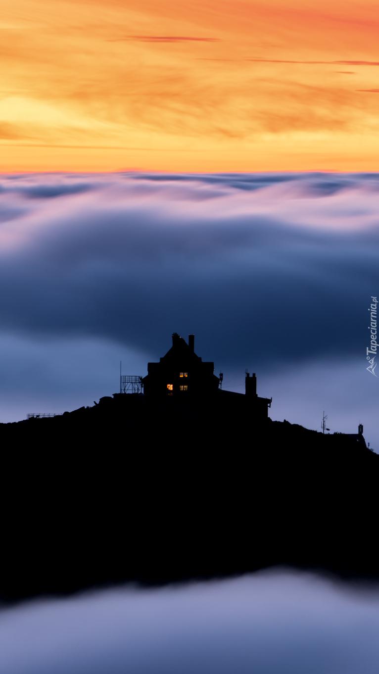 Dom na wzgórzu między chmurami