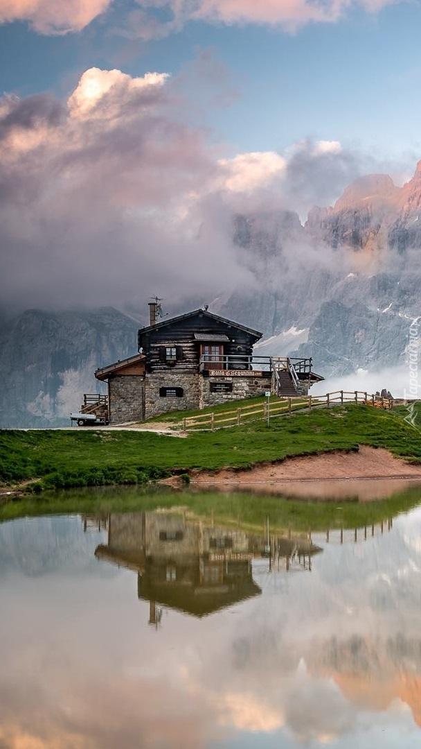 Dom nad jeziorem na tle zamglonych gór