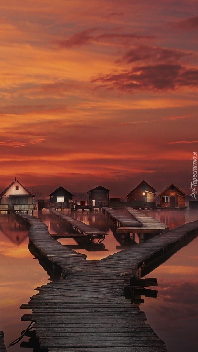 Domki na palach nad morzem o zachodzie słońca