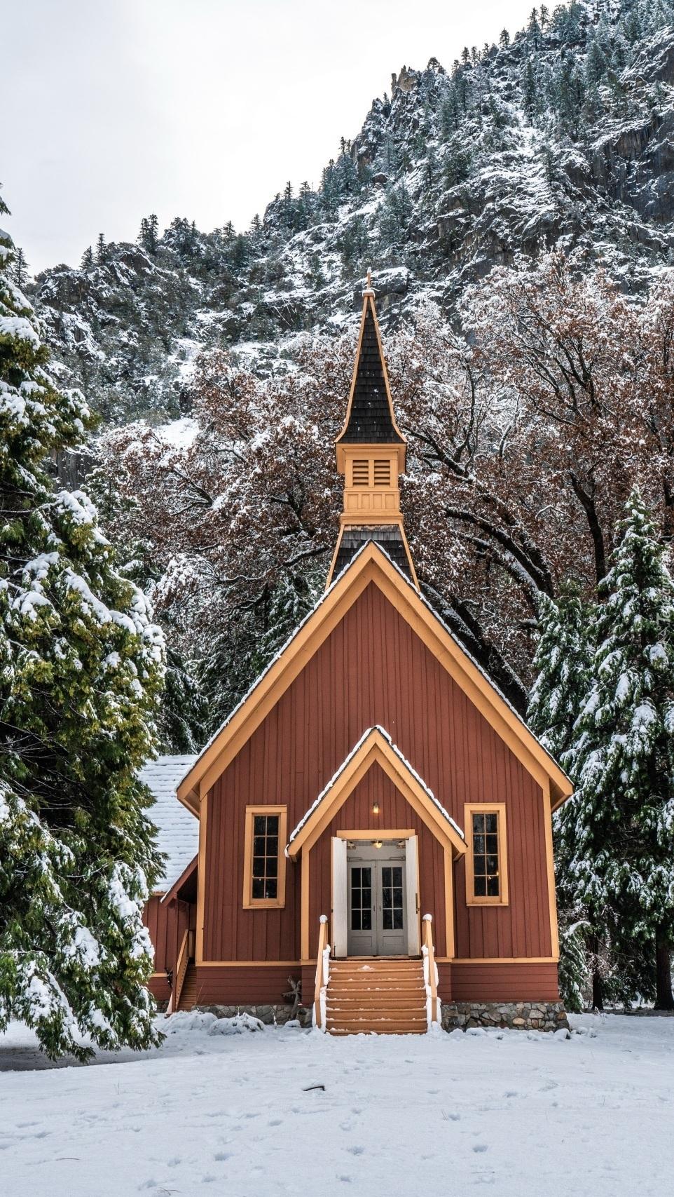 Drewniana kapliczka z wieżyczką na tle lasu zimą