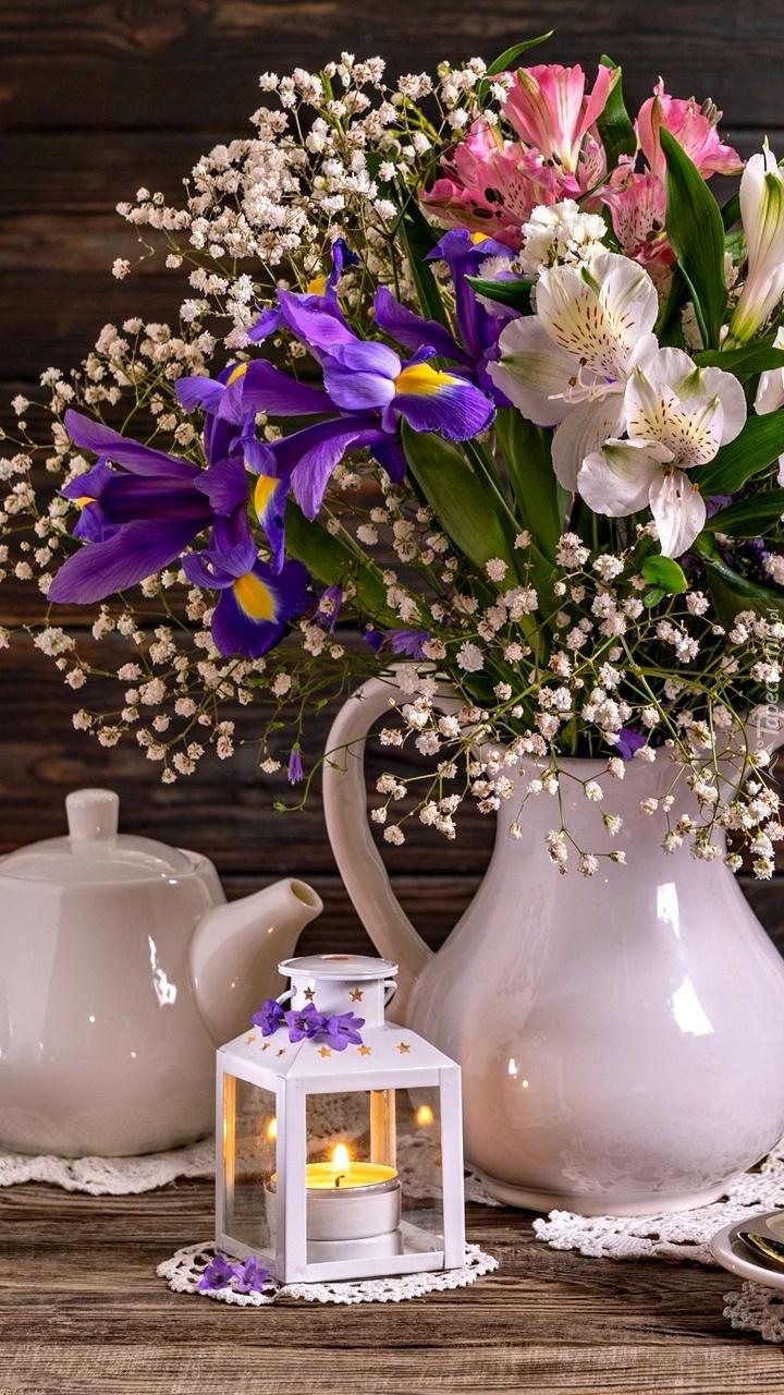 Dzbanek z kwiatami obok lampionu
