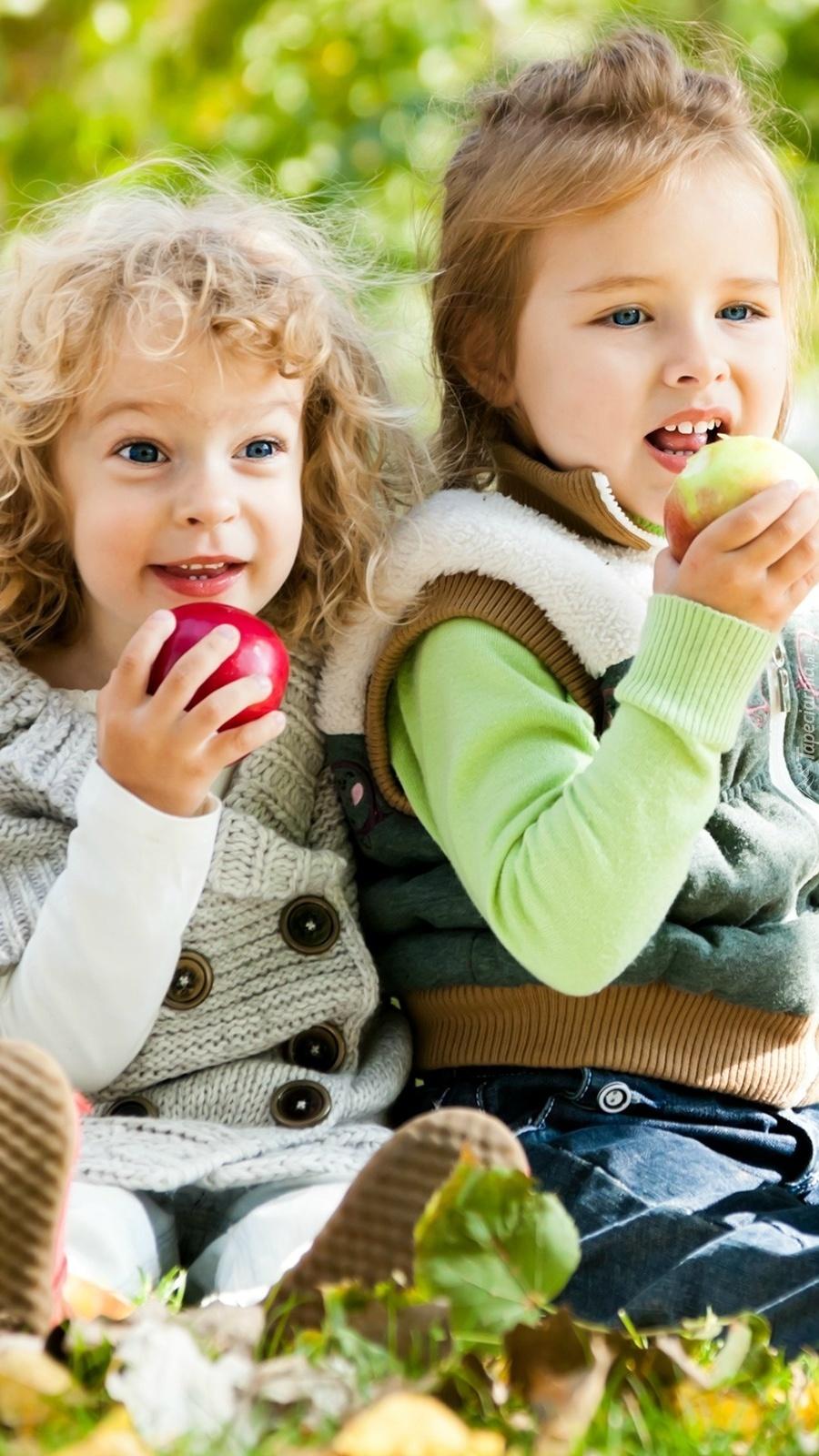 Dzieci na łące z jabłkami w rękach