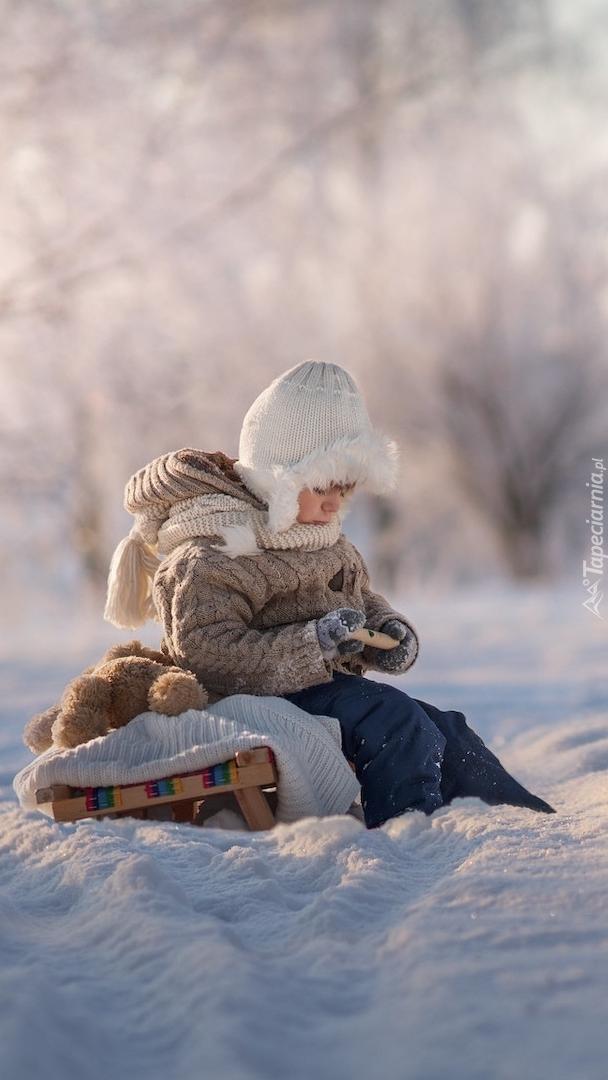 Dziecko na sankach w śniegu